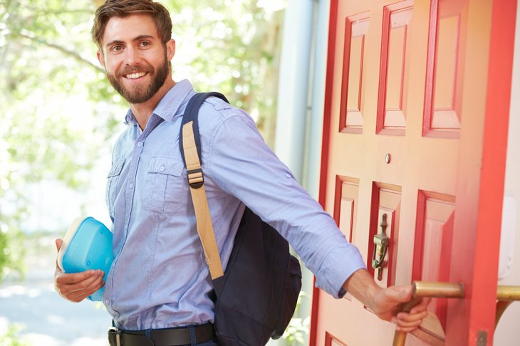 A young man leaves home with a backpack and lunch