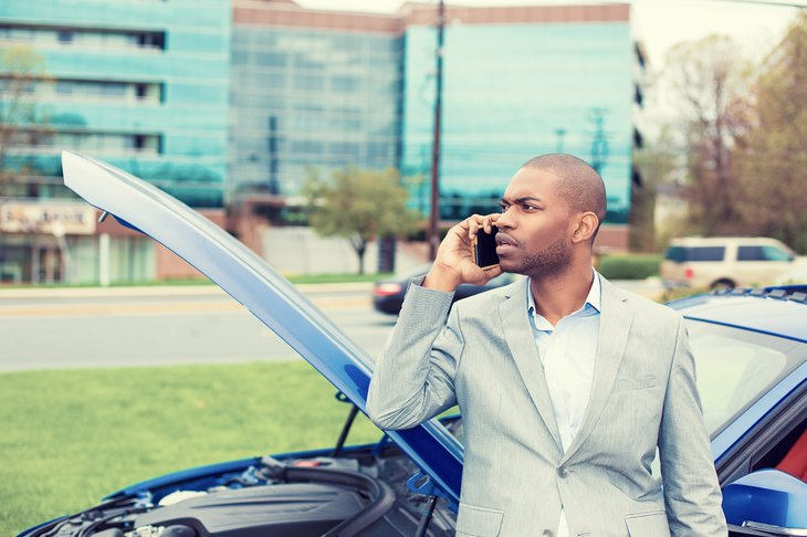 Man leaning against car with hood open, making a call.