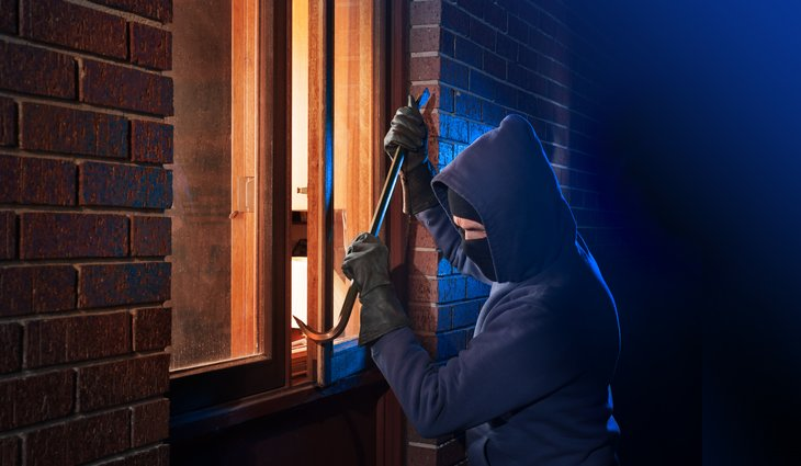 Burglar using crowbar to pry open window