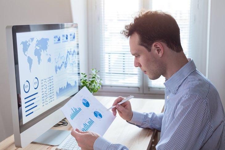A man studies financial data at his computer