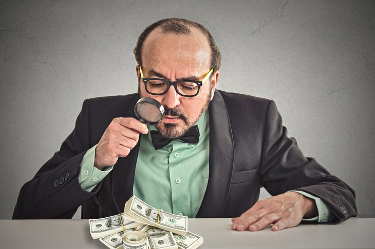 Businessman looking at cash with a magnifying glass