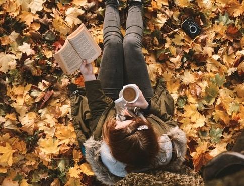 girl with coffee reading book near tree